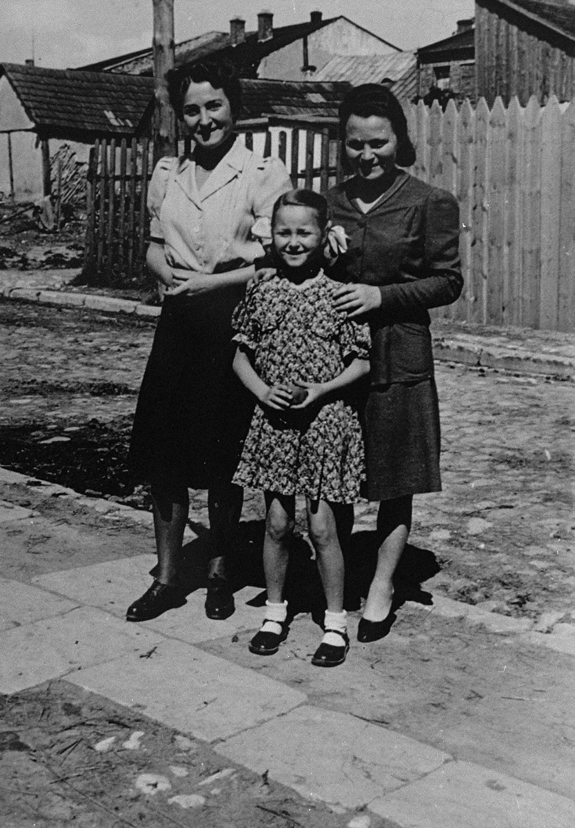 Jewish survivors pose on a street in Busko-Zdroj.  Pictured are Laura Schwarzwald (left) with her daughter Selma (middle) and sister Adela Litwak (right).