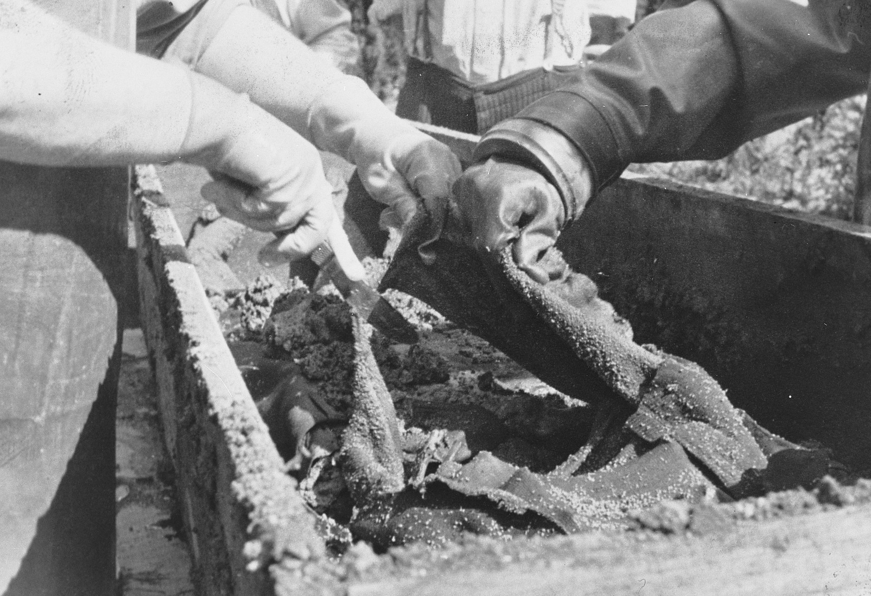 Members of the an Army War Crime Investigation team examine the remains of American flyers somewhere in Germany.
