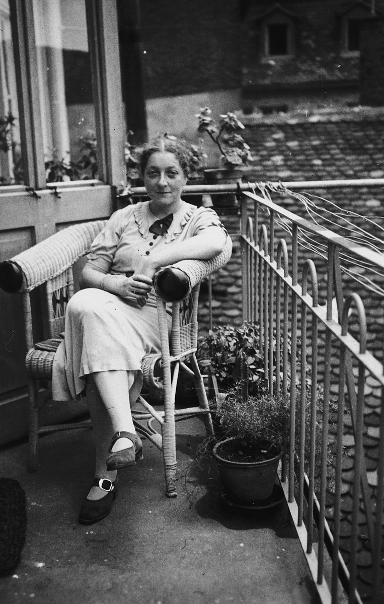Portrait of a Jewish woman sitting in a wicker chair on the terrace of her apartment in Germany.  Pictured is Karoline Keller.