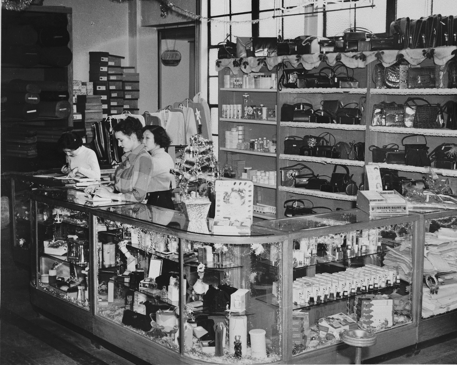 Chinese and Jewish female employees work behind the counter of the Ponvey Department store in Tientsin.
