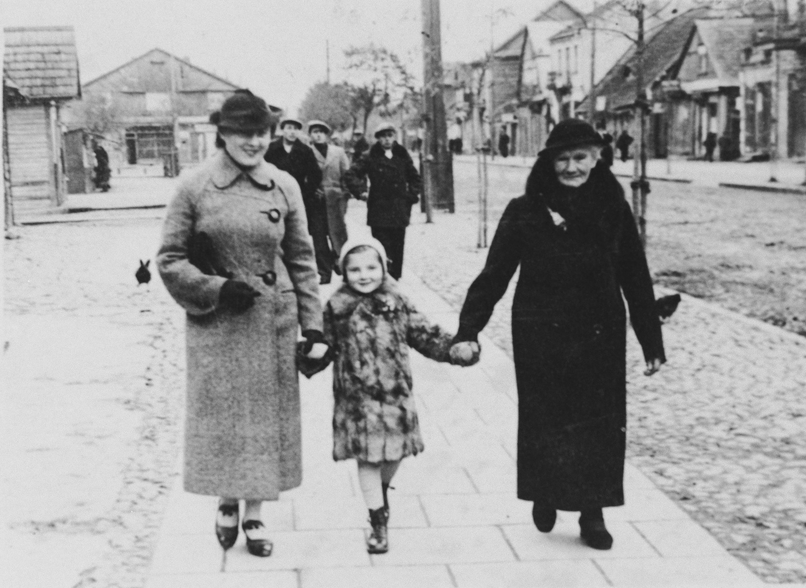 Three generations of a Polish-Jewish family walk down a street in Bielsk Podlaski.  From left to right are Genia Kac Storch, Helena Storch and Tzivia Kac.