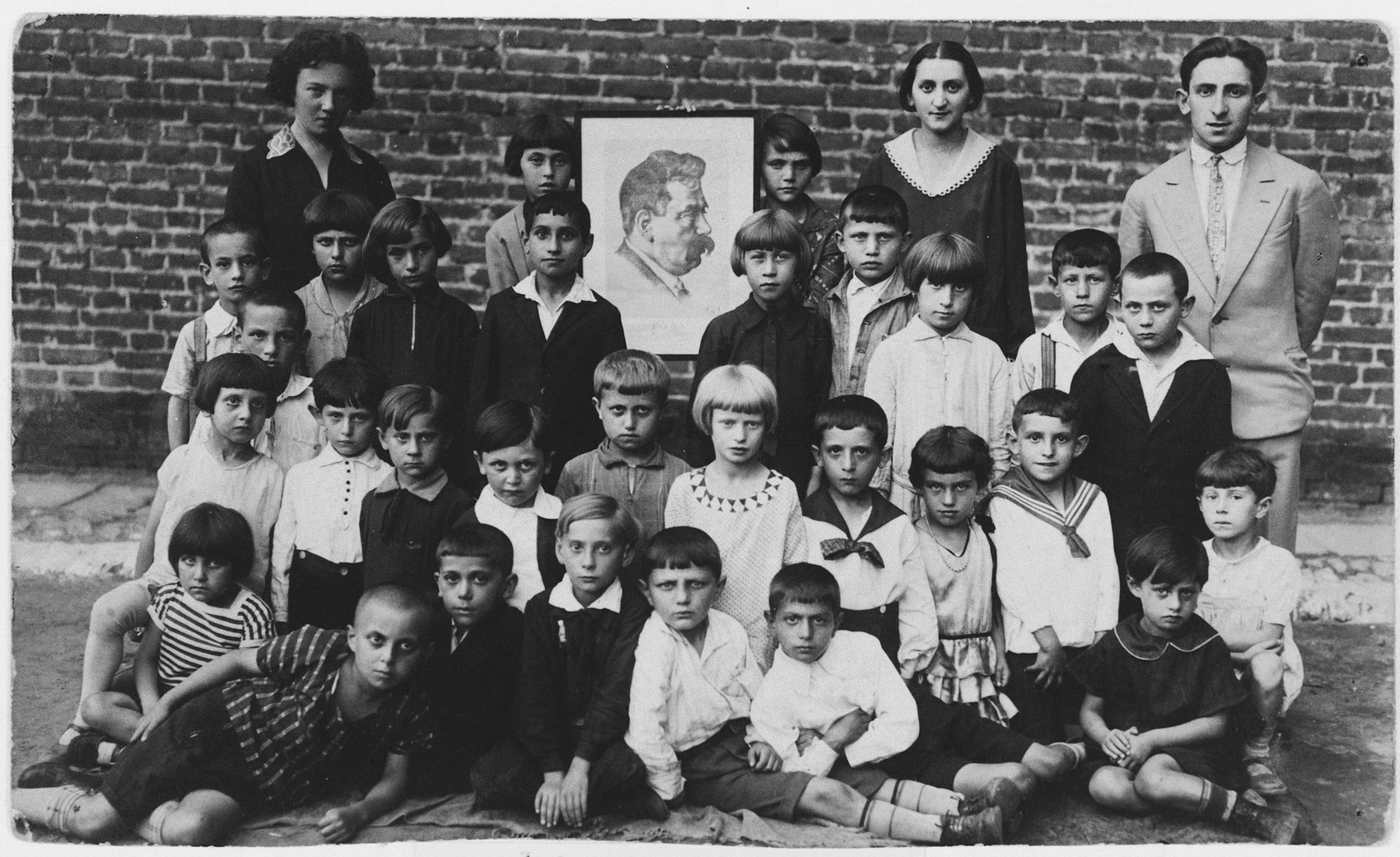 Group portrait of the first-grade class of the Bundist school in Kalisz.  Standing on the left is their teacher Genia Kac.  Standing on the far right is the school secretary, Heniek Storch.  The portrait is of the Yiddish writer, Y.L. Peretz.