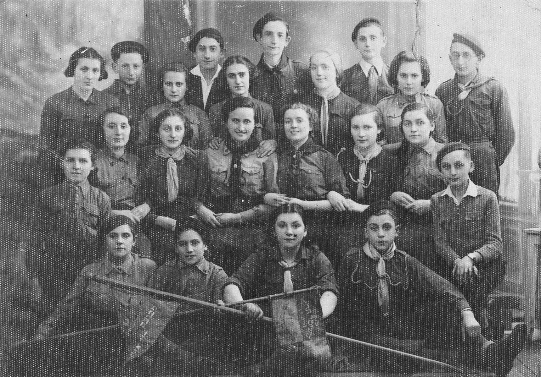 Group portrait of members the the Hasmonean chapter of the Hashomer Hadati religious Zionist youth movement in Dabrowa Gornicza, Poland.  Pictured in the top row from right to left are: Zvi Rechnic, Hercko Lenczner, Lewkowicz, Moniek Rozen and Moniek Szeps; in the second row from the top, from right to left are: Frumka Kener and L. Tenenbaum, others unknown; in the third row from the top, from right to left are: Jakub Bajtner (kneeling), Miriam Oks, Miriam Bajtner, Dwora Oks and Chava Bajtner; in the front row are Motek Ostrowiecki, Sala Gottlieb, Chanan Kener, and unknown.