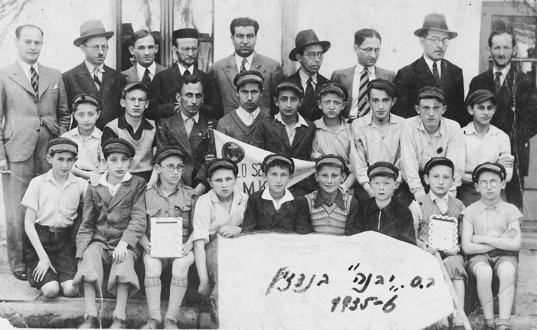 """Group portrait of faculty and students of the Yavne Hebrew elementary school in Bedzin, Poland.  Among those pictured is Moniek Szeps (front row, second from the right) holding a framed portrait of the Polish president.  The inscription on the back of the photo reads, """"As a memento to dear Moniek wishing that you will visit often your Mizrachi teacher, Euteniusz Pejsachowicz.""""  It is followed by a list of student signatures: H. Przymowski, M. Lustiger, Ksylek Hinigman, Moniek Radzynski, Olek Maka, H. Rechnic, M. Rechnic, Braun."""