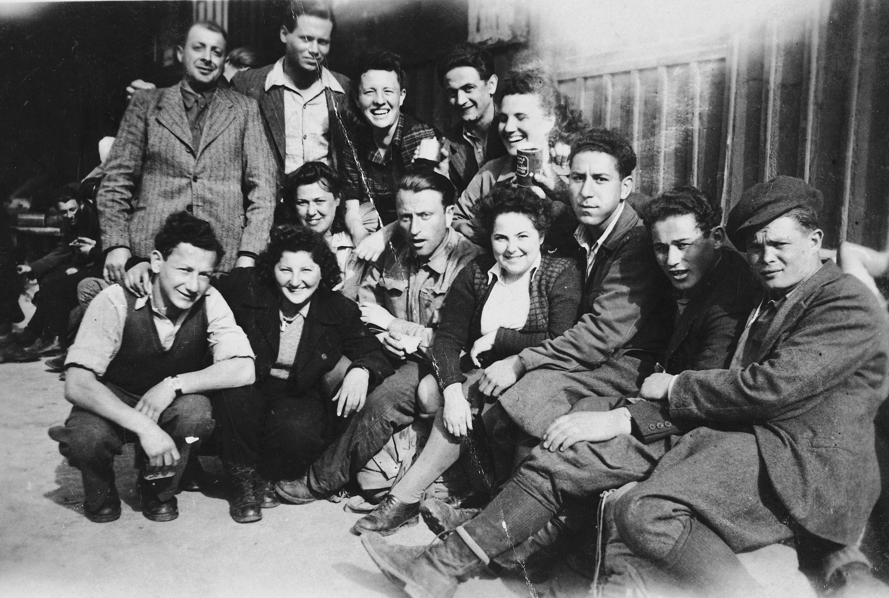 Group portrait of young Jewish DPs who are seeking to immigrate to Palestine illegally, at a way station near the Italian border.  They await permission to cross the border and transport into Italy.  Seated in the front row from left to right are: Moniek Szeps, Goldi Silberstein, Levi Danielski, unknown, Meni Szmulewicz, Mendel Ingber and Tesler; in the second row, from left to right are: Zlotnik, Arik Ofner, Hana, Mojszale Wyszogrodzki, Haja Danielski; seated above Goldi Silberstein is Hana Ingber.