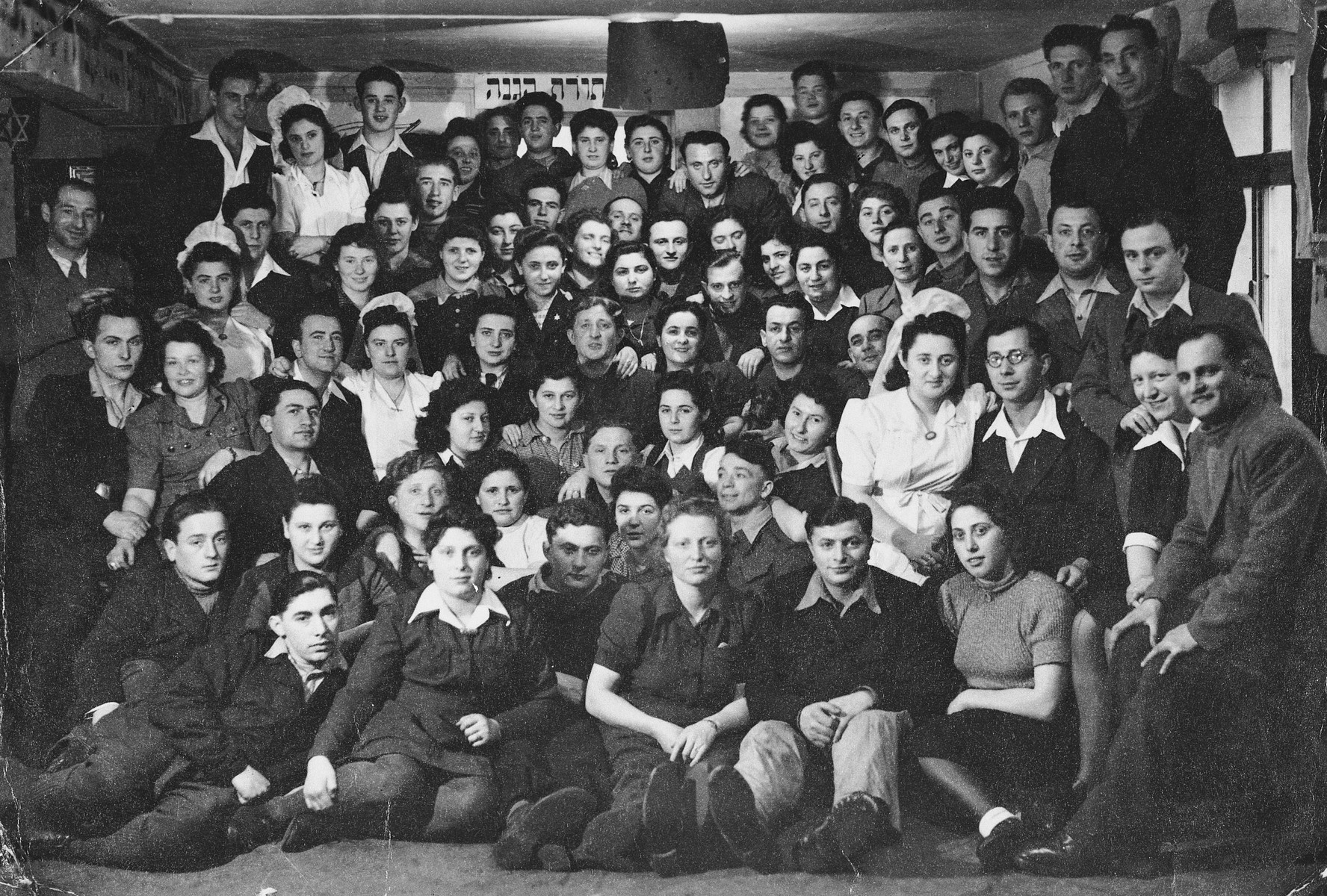 Group portrait of members of the Kibbutz Buchenwald hachshara (Zionist collective) in Geringshof, Germany, taken on the occasion of the marriage of four of its couples.