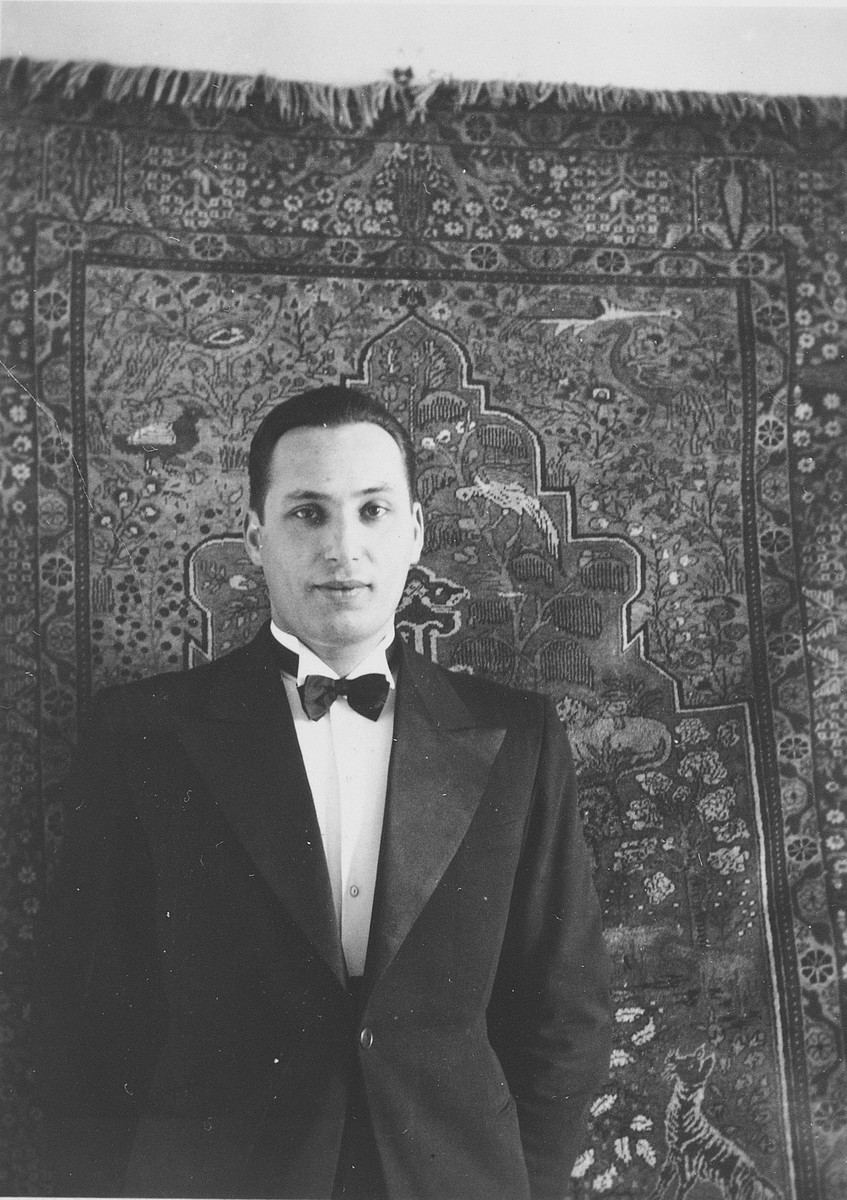 Edmund Dresner poses in his home in Zagreb beneath an Oriental rug which is hanging on the wall .