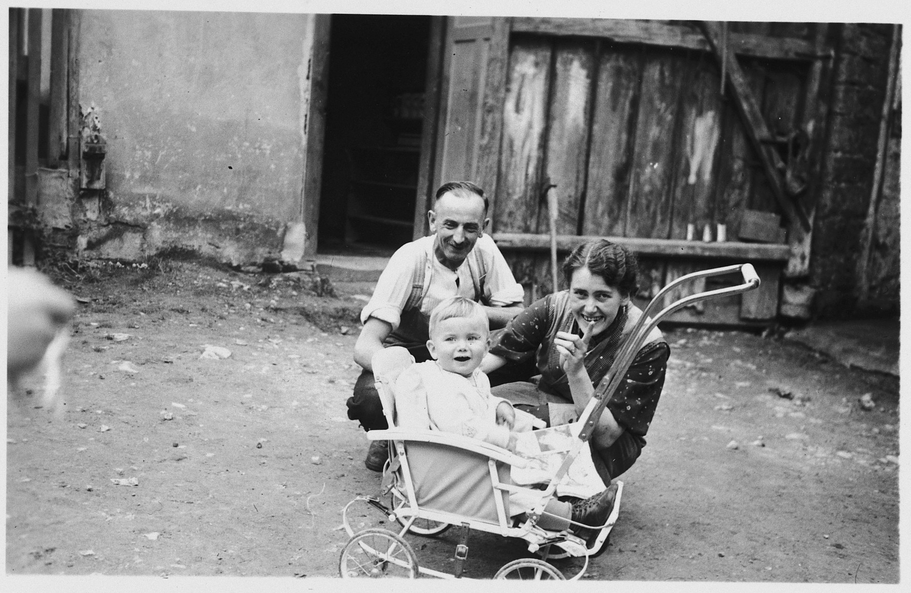 A Jewish family poses with a toddler in a stroller outside a barn.  Pictured is the Keller family.