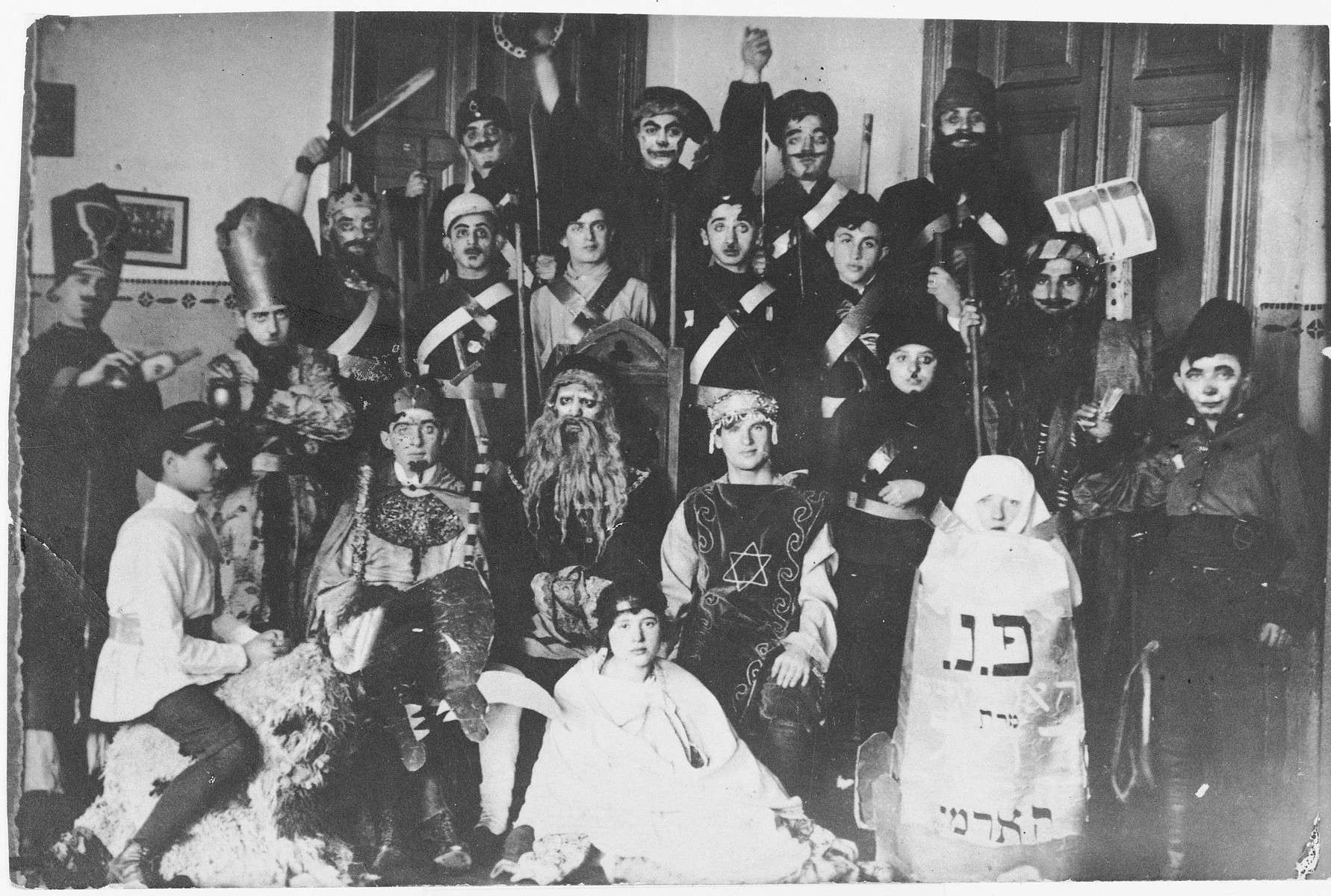Students from the Vilner Lerer Seminar (Yiddish Teachers' Seminary) perform a Purim play.  Among those pictured are Y. Trupianski, Goldberg, Y. Mann, Rosenberg, Batke, Genia Kac (second from the right with Hebrew letters on her costume).