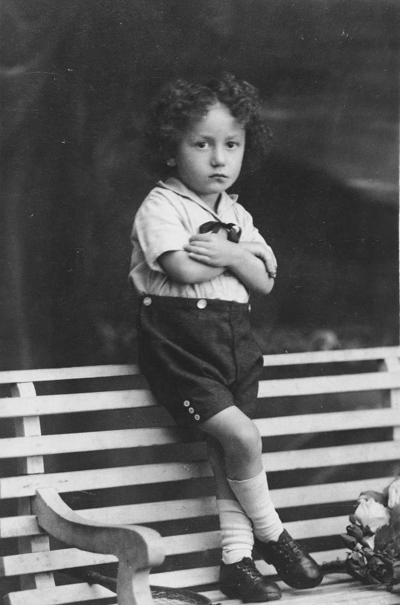 Studio portrait of a young Jewish boy standing on a park bench in Dabrowa Gornicza, Poland.  Pictured is three-year-old Moniek Szeps.