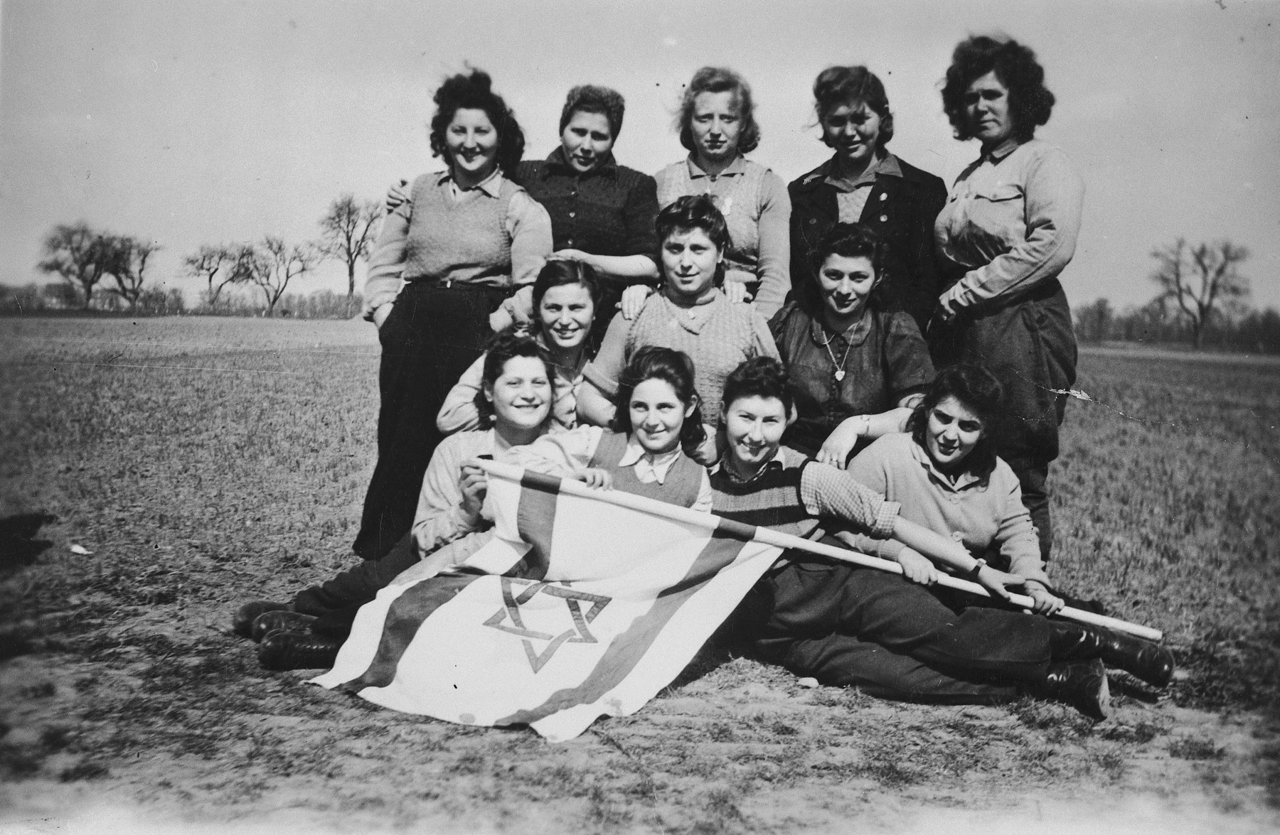 A group of young Jewish DPs who are seeking to immigrate to Palestine illegally, pose outside in a field with a Zionist flag.  Pictured in the front row from left to right are Kicia, Renia Klugman, Sabina Szeps, Sara Klugman; middle row: Ester Goldschmidt, Mina Kokodinska, Hanka Wiernik Schlesinger; top row: Goldi Silberstein, unknown, Dora, unknown, Bracha.