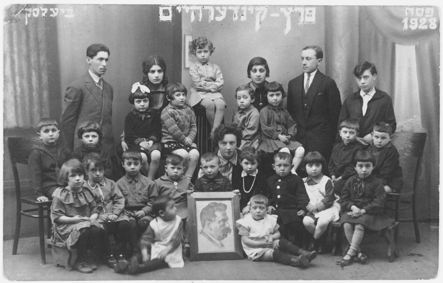 Kindergarten children and teachers in the Y.L. Peretz Yiddish school in Bielsk-Podlaski.  Seated in the center is their teacher Genia Kac.