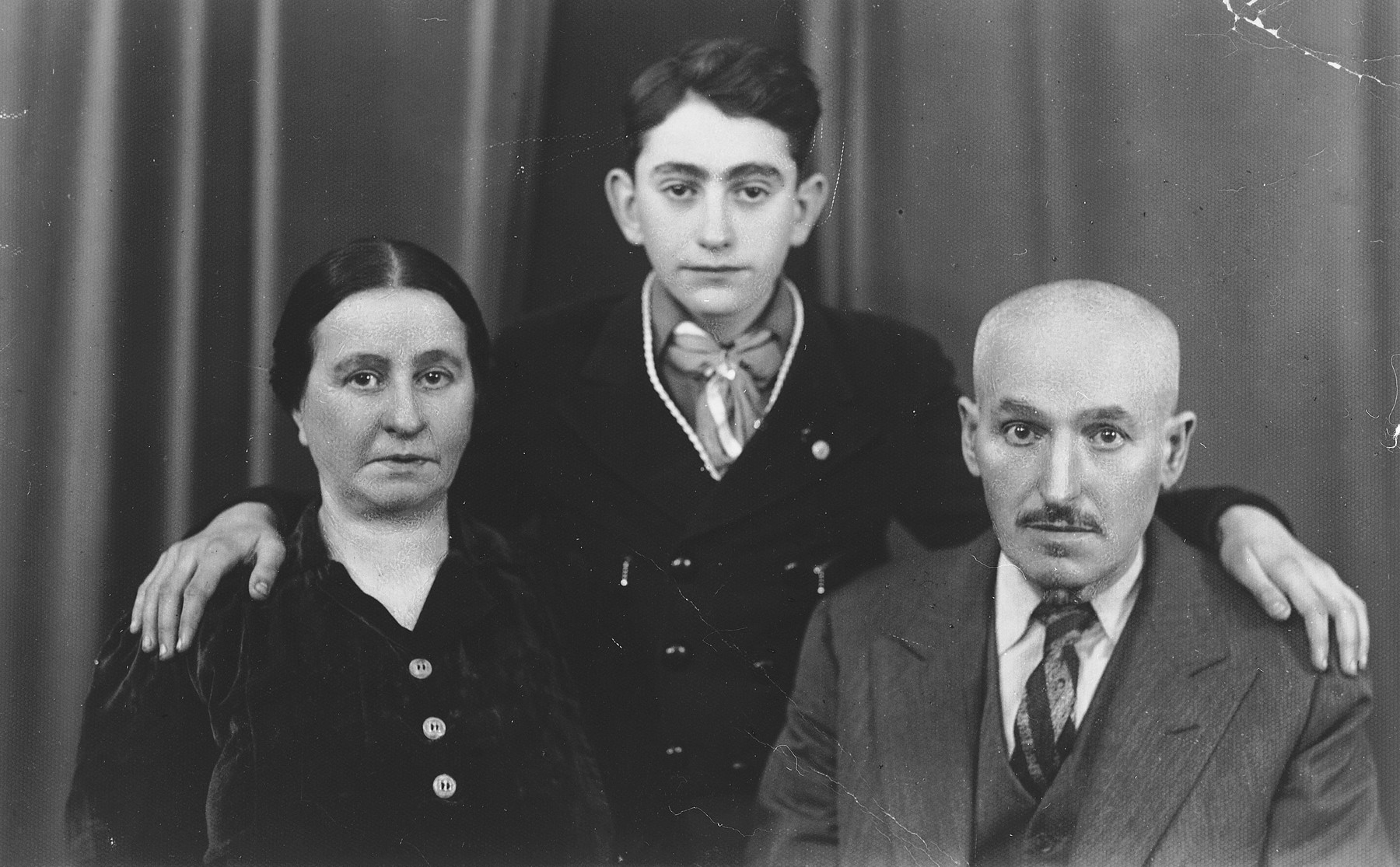 Shmuel Shalkovsky poses between his parents in his Hashomer Hatzair uniform.