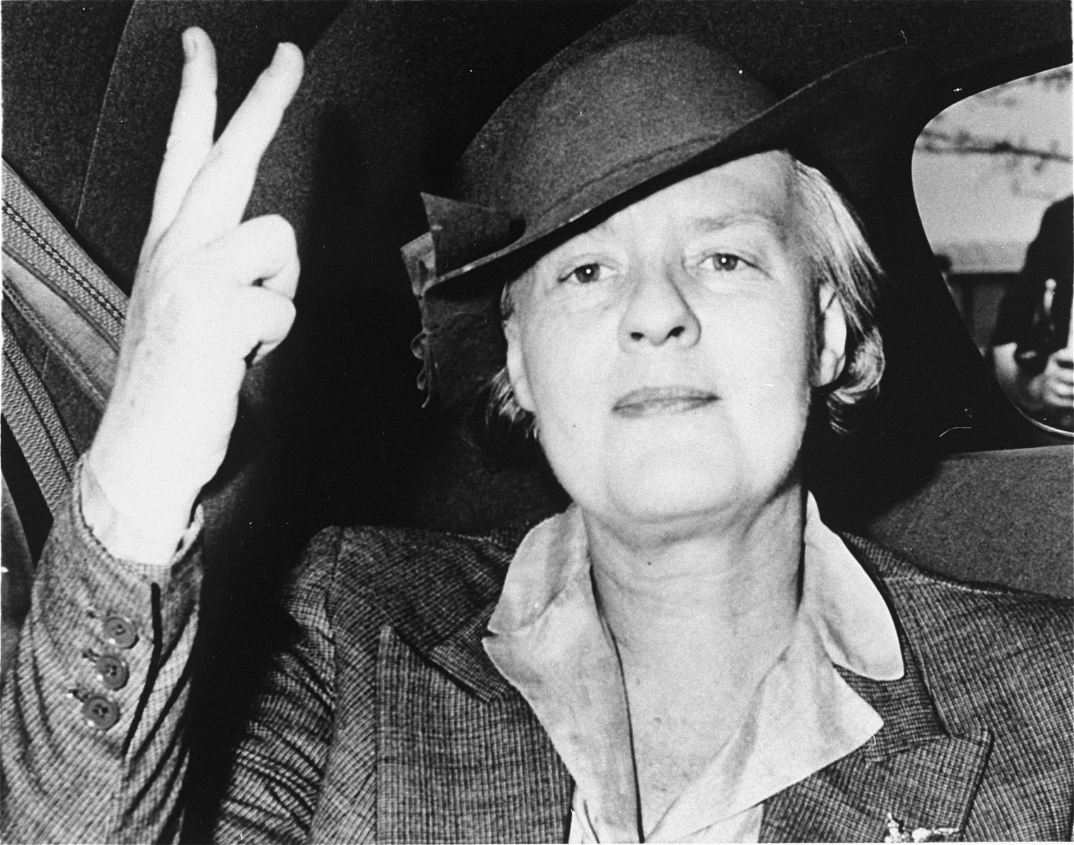 """Portrait of Dorothy Thompson making a """"V for Victory"""" sign and riding in a car."""