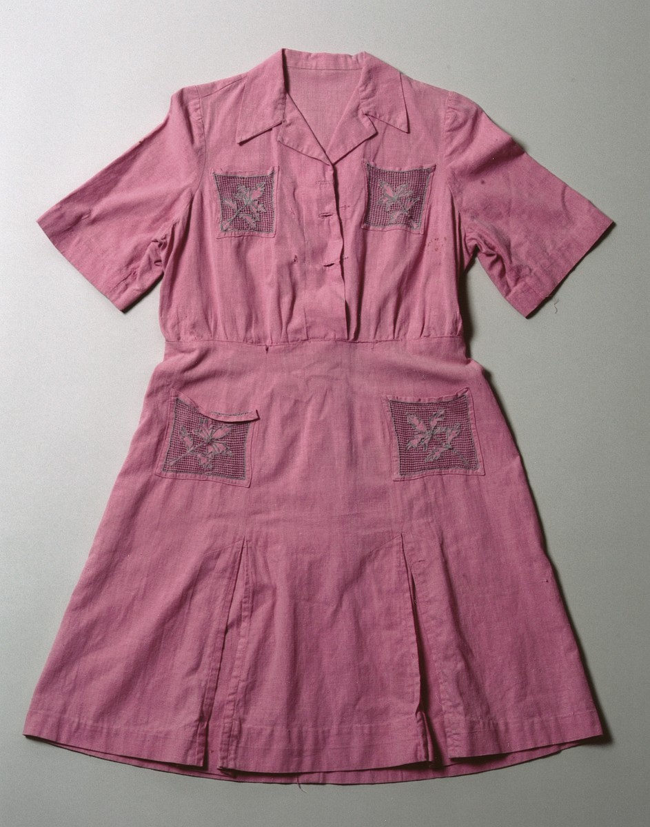 Pink embroidered Sabbath dress made from a flour sack by Greek Jewish survivors Sarina and Dora Levy in postwar Athens.  Since new clothing was beyond their means to obtain, Sarina and Dora seized upon the idea of using flour sacks from a nearby warehouse for fabric.  Sarina washed the sacks and colored them with a red dye.  Afterwards, Dora, who had supported herself in hiding as a dressmaker's apprentice, cut the sacks and fashioned a dress for herself.  She then proceeded to embroider the pockets to give it a more festive look.  For several years Dora wore this dress as her special Sabbath garb.  In February 2003 Dora Levy (now Saltiel) donated this dress to the Museum along with a cache of personal papers and photographs documenting the experience of her once large, extended family from Salonika.