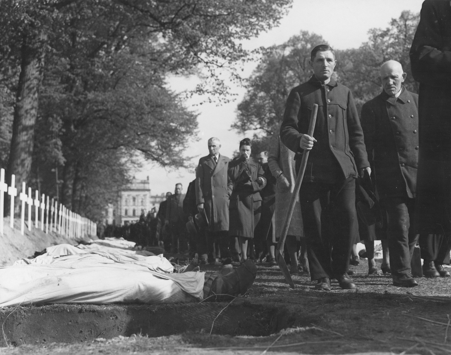 Upon the orders of the U.S. Army, the population of Ludwigslust files past the bodies of prisoners killed in the Woebbelin concentration camp, which have been laid out for burial in individual graves on the palace grounds of the Archduke of Mecklenburg.  The men carry shovels to bury the victims.