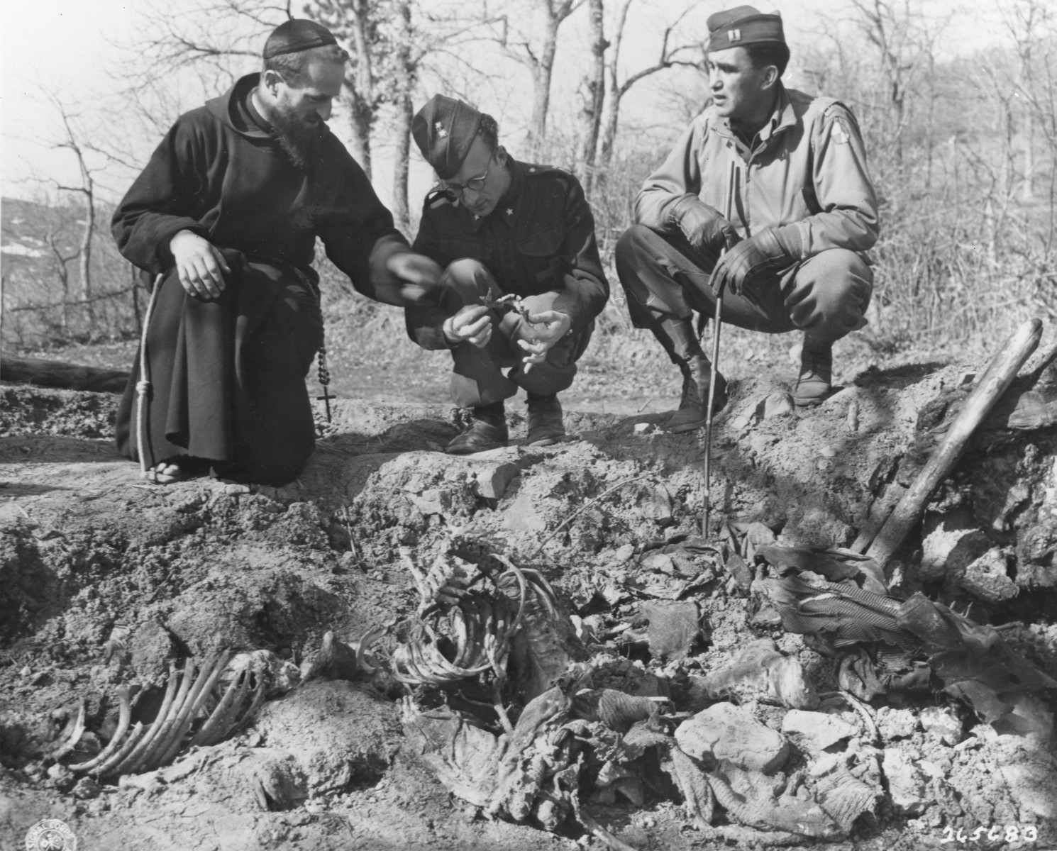 Padre Enrico Farneti, a local priest, Chaplain Enrico Dino, Italian Army, and Capt. Labre Garcia, the investigating officer from the U.S. Military Government, examine a grave containing the remains of at least two Italian civilians killed and burned by German forces.
