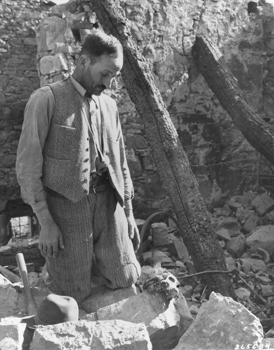 Narcisso Palmonari, an Italian civilian, looks at the remains of his child, Ines, who was killed and burned by German forces along with about 80 other Italian civilians.
