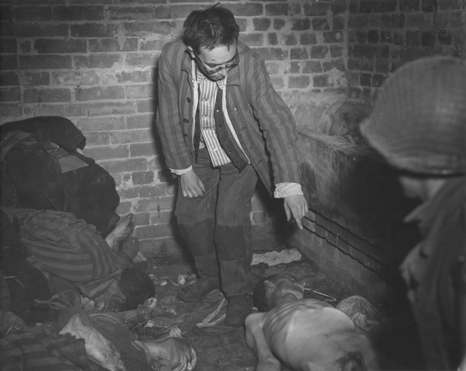 David Rousset, a liberated prisoner who is acting as a guide for an American soldier, points out the emaciated corpse of a prisoner lying on the floor of a brick structure in the newly liberated Woebbelin concentration camp.