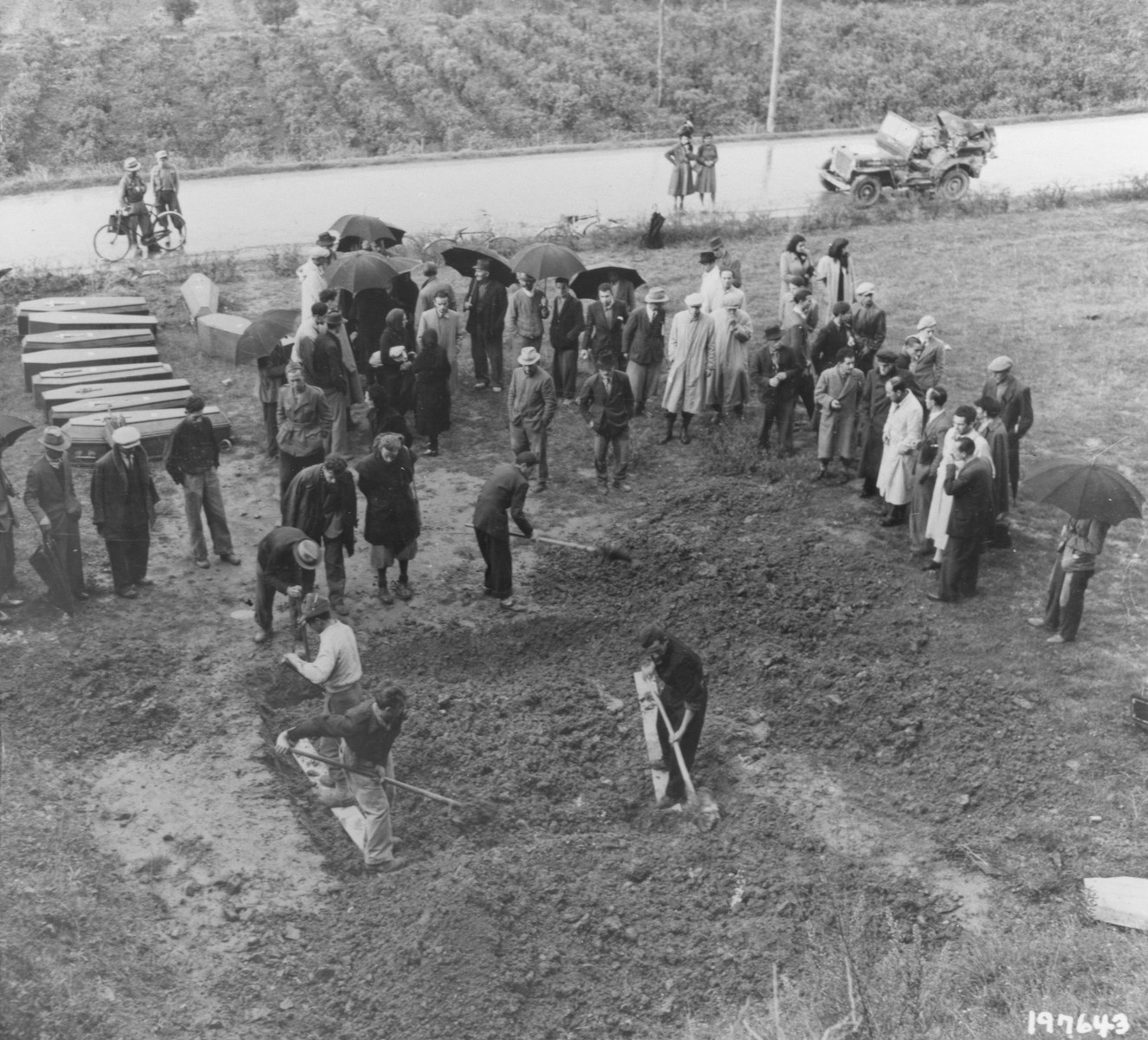 Italian civilians exhume a mass grave containing the bodies of 38 Italians shot by German forces.    The victims were chosen at random and killed in reprisal for the murder of an Italian Fascist by partisans in August 1944.  A young Italian woman who protested the killings to the Germans was shot along with the other hostages.