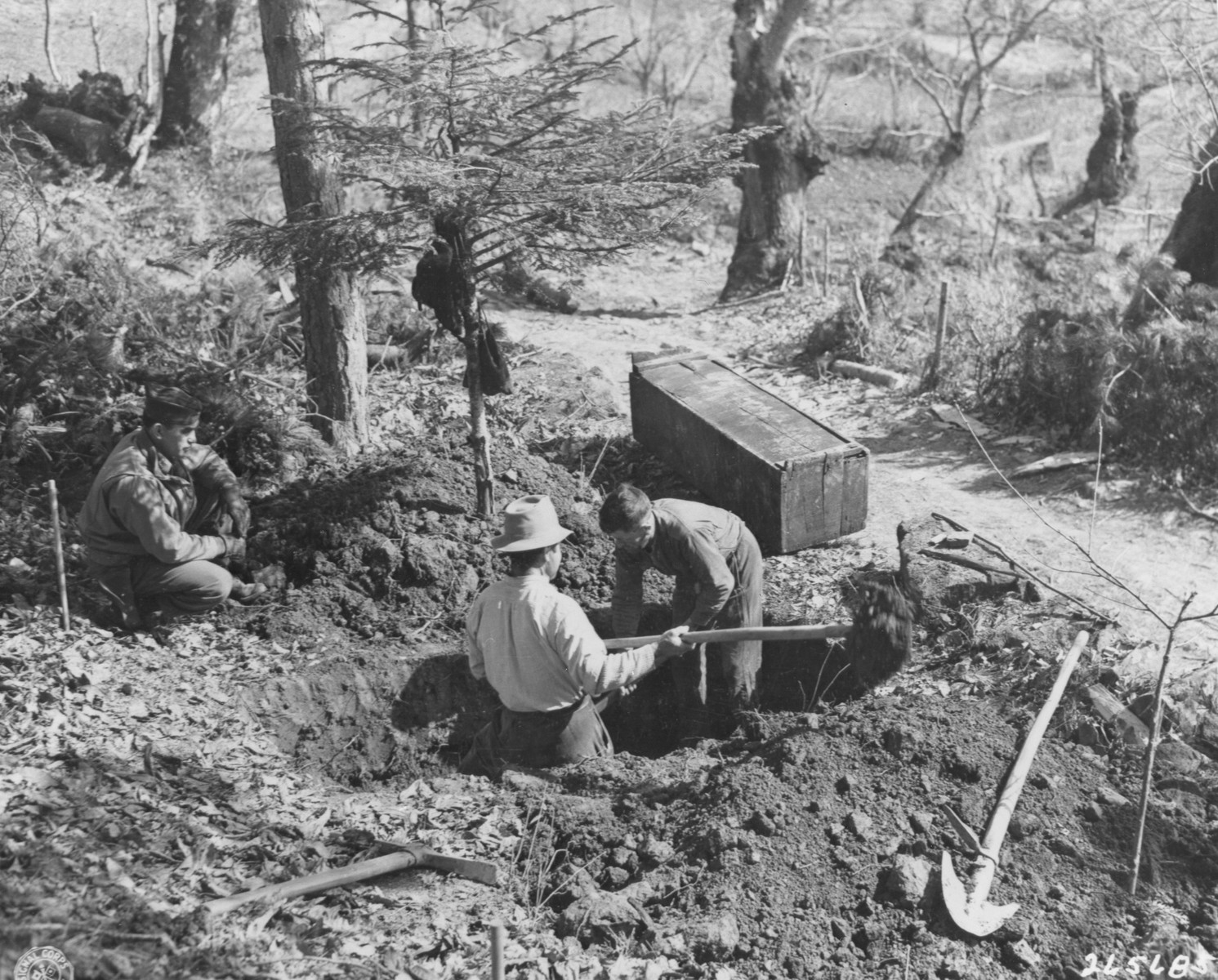 Capt. Labre Garcia, investigating officer of the U.S. Military Government, looks on as Italian workmen dig a grave for one of 82 Italian civilians killed and burned by German forces.