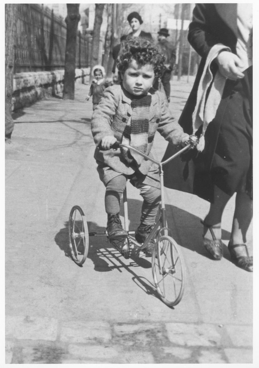A young Jewish boy rides his tricycle down a street in Krakow.  Pictured is Lolush Gerstner, who was later killed in Auschwitz.