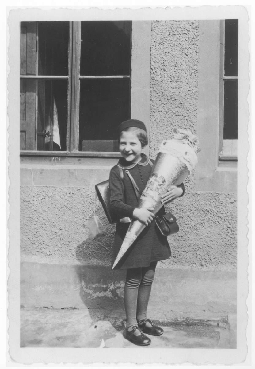 Ursula Klipstein poses holding the traditional Schultuete [a school cone] filled with candies on her first day of school.