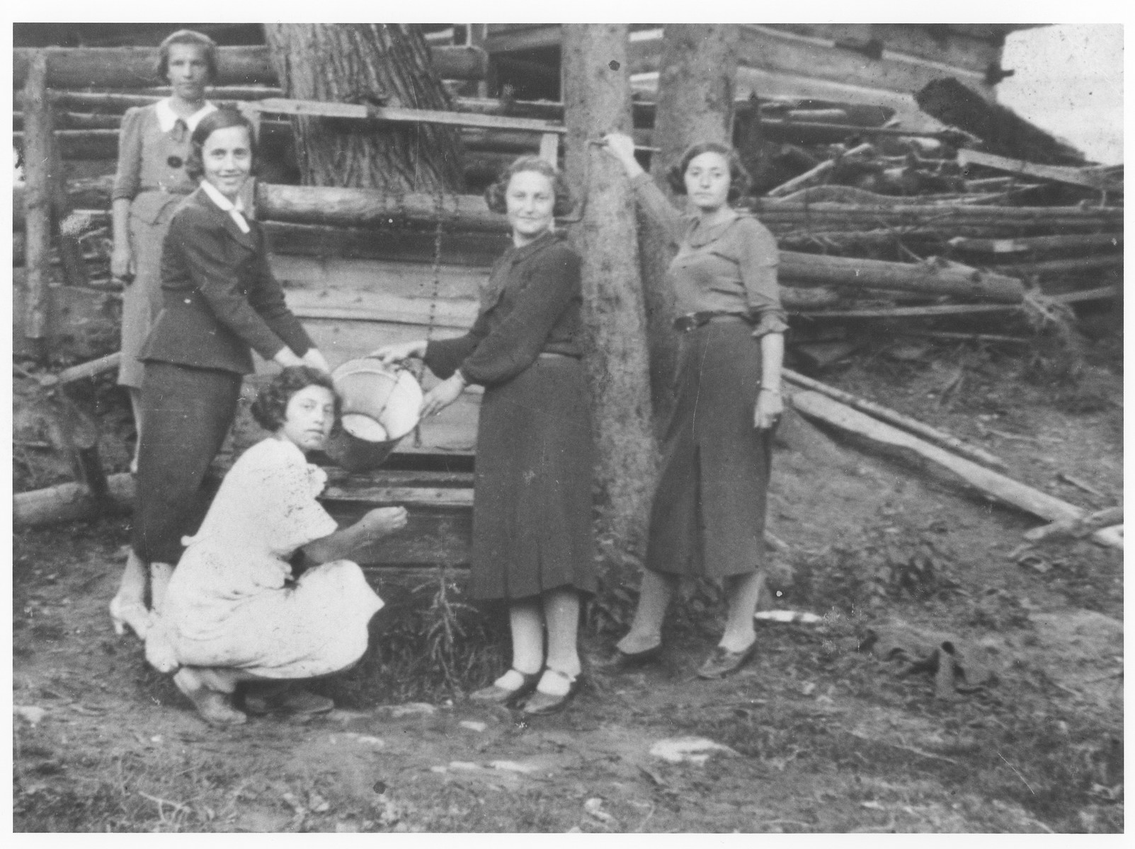 Five friends from the Beit Yaakov school draw water from a well in Zakopane.   Among those pictured is Gusta Gerstner.