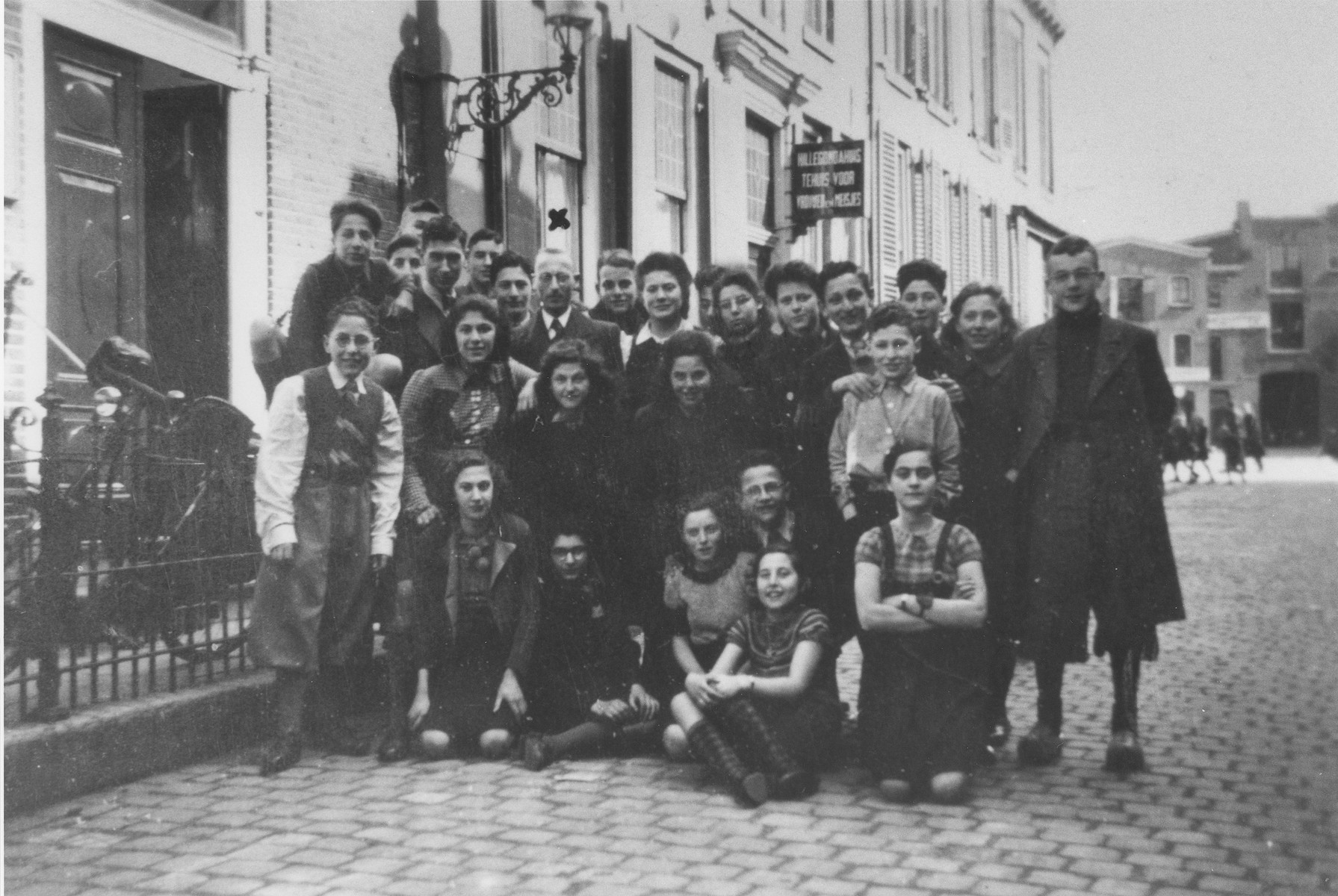 Students of the Jewish school of Zwolle pose on the street outside the school building.  Among those pictured are the bookkeeping teacher, Mr. Hershel (under the X) and Doris Bloch (front row, right).