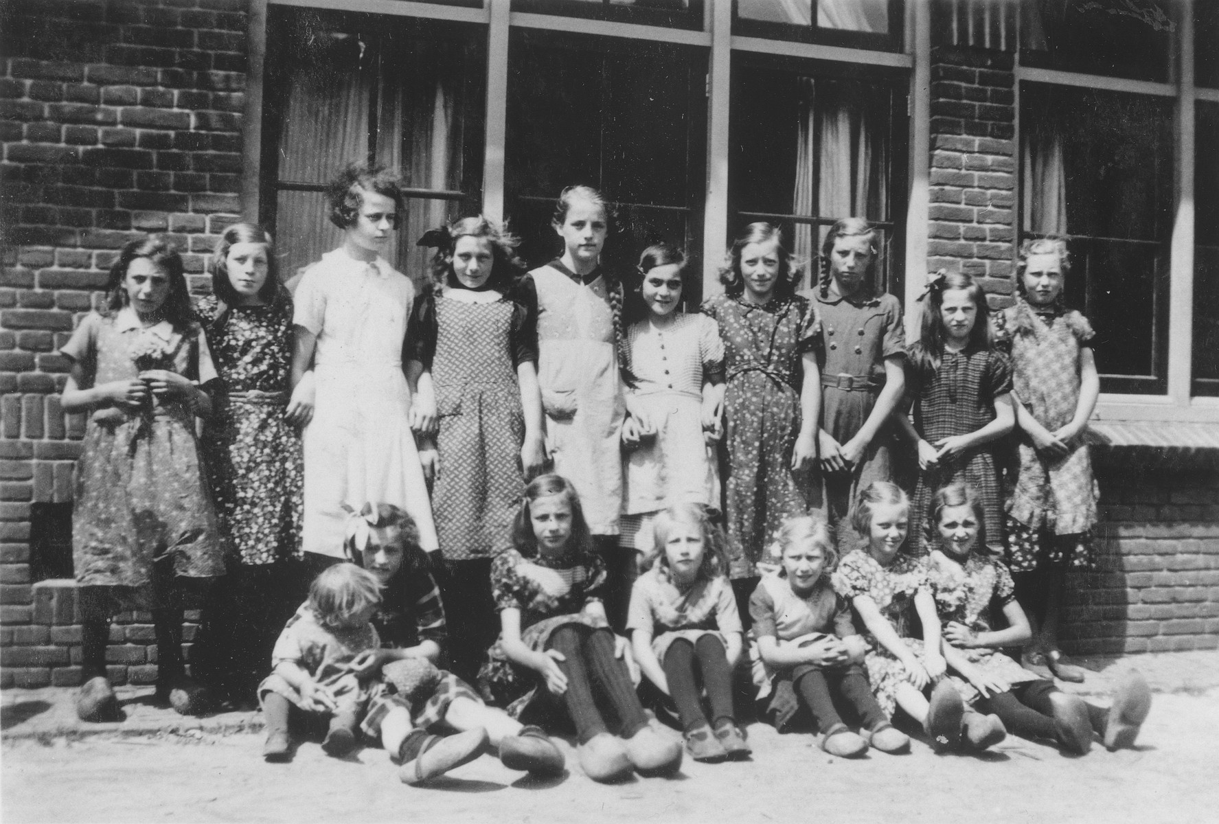 Two German Jewish refugee girls appear in a class photo of a village school in Hulshorst, Holland.  Gerda Bloch is pictured standing third from the left, and Doris Bloch is fifth from the right.