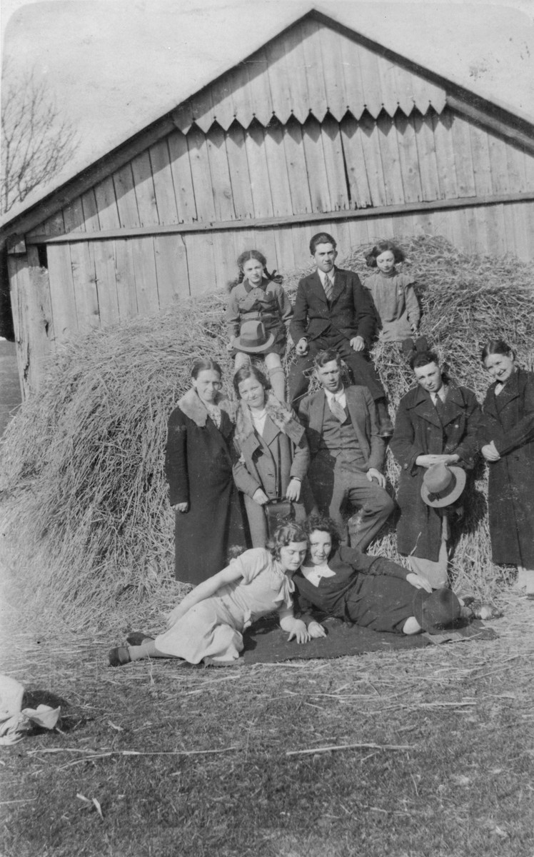 A group of Jewish youth pose on a haystack at a summer camp in Raczyna, Poland.   Among those pictured is Basia Gurfein (bottom, right).
