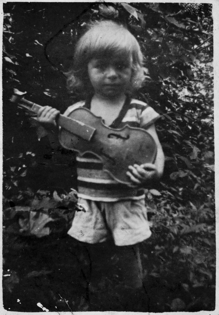 Portrait of a young Jewish child holding a violin in Bilki.  Pictured is Edward Mermelstein.