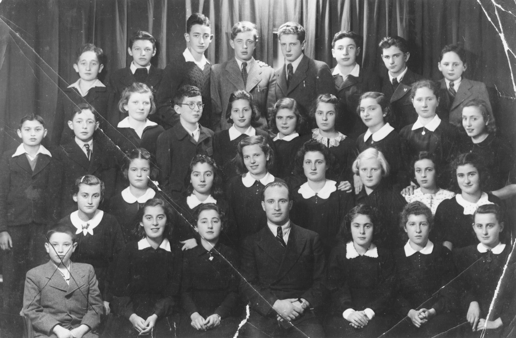 Group portrait of the students of the Schwabes Hebrew gymnasium in Kovno, Lithuania.  Among those pictured is Ben Zion (Nolik) Schmidt (top row, second from the right). Freda (Shottenstein) Schatenstein (second row from bottom, fourth person from right).