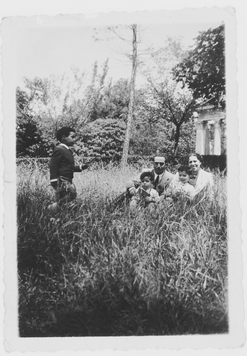 The Tagliacozzo family relaxes in a garden.  Seated are Giovanni Dell'Ariccia and Adele Tagliacozzo Dell'Ariccia and their sons David and Leilo.  On the left is their nephew David Tagliacozzo.
