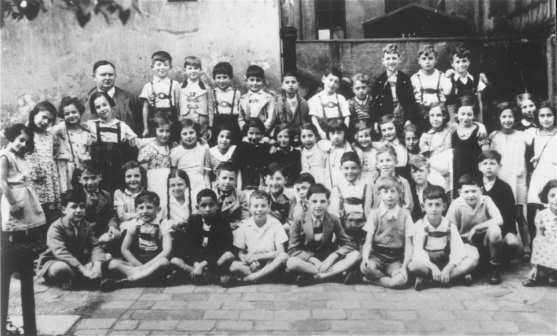 Class portrait of the third grade at the Juedische Volksschule in Munich.   On November 25, 1941 sixteen of these children were sent to Kaunas, Lithuania, where they were shot in the Ninth Fort.  Among those pictured are: top row: the teacher, Julius Kissinger (top row, left); Jacki Alster (top row, second from the left), Manni Busch (top row, third from the left), Manni Busch's younger brother (top row, fourth from the left), Erich Kupfer (an orphan from the Jewish orphanage in Munich, who was later deported to Auschwitz, top row, fourth from the right), and Harald Zernik (who was also deported to Auschwitz).  Second row from the top: Ester Berger (an orphan who was later deported to Auschwitz, left), Ricki Leidel (third from the left), Eva Blutenberg and her sister Ruth (eighth and ninth from the left), Susie Scherz (ninth from the right), Bertl Sandbank (who was later deported to Auschwitz, fourth from the right).  Third row from the top: Guenter Hess (left), Manfred Pollak (an orphan, who was later deported to Auschwitz, eighth from the left), and Hilde Weissmann (at the extreme right). [oversized print]