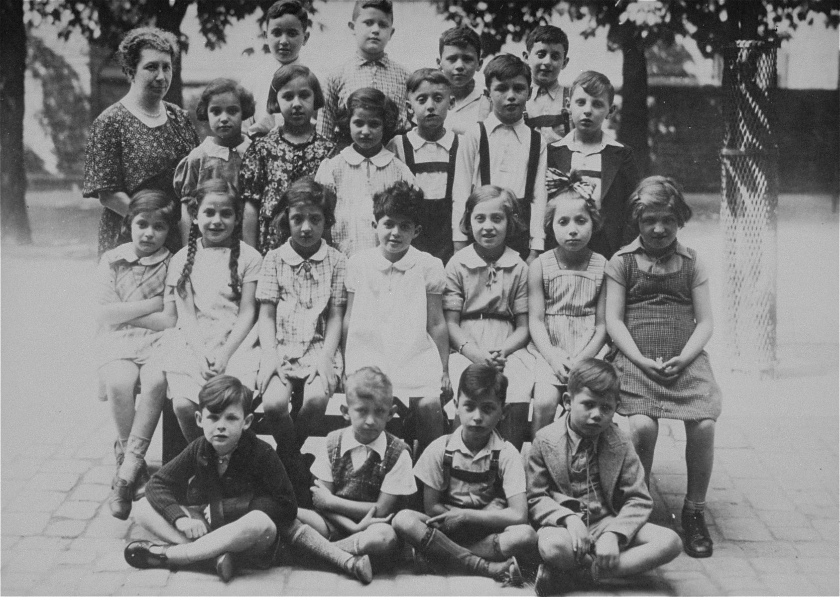 Group portrait of pupils in the first grade at a Jewish school in Karlsruhe, Germany that had been relocated to one floor at the 'Holzbodengymnasium' a special school for mentally disabled children.   Among those pictured is the teacher, Flora Hirsch.