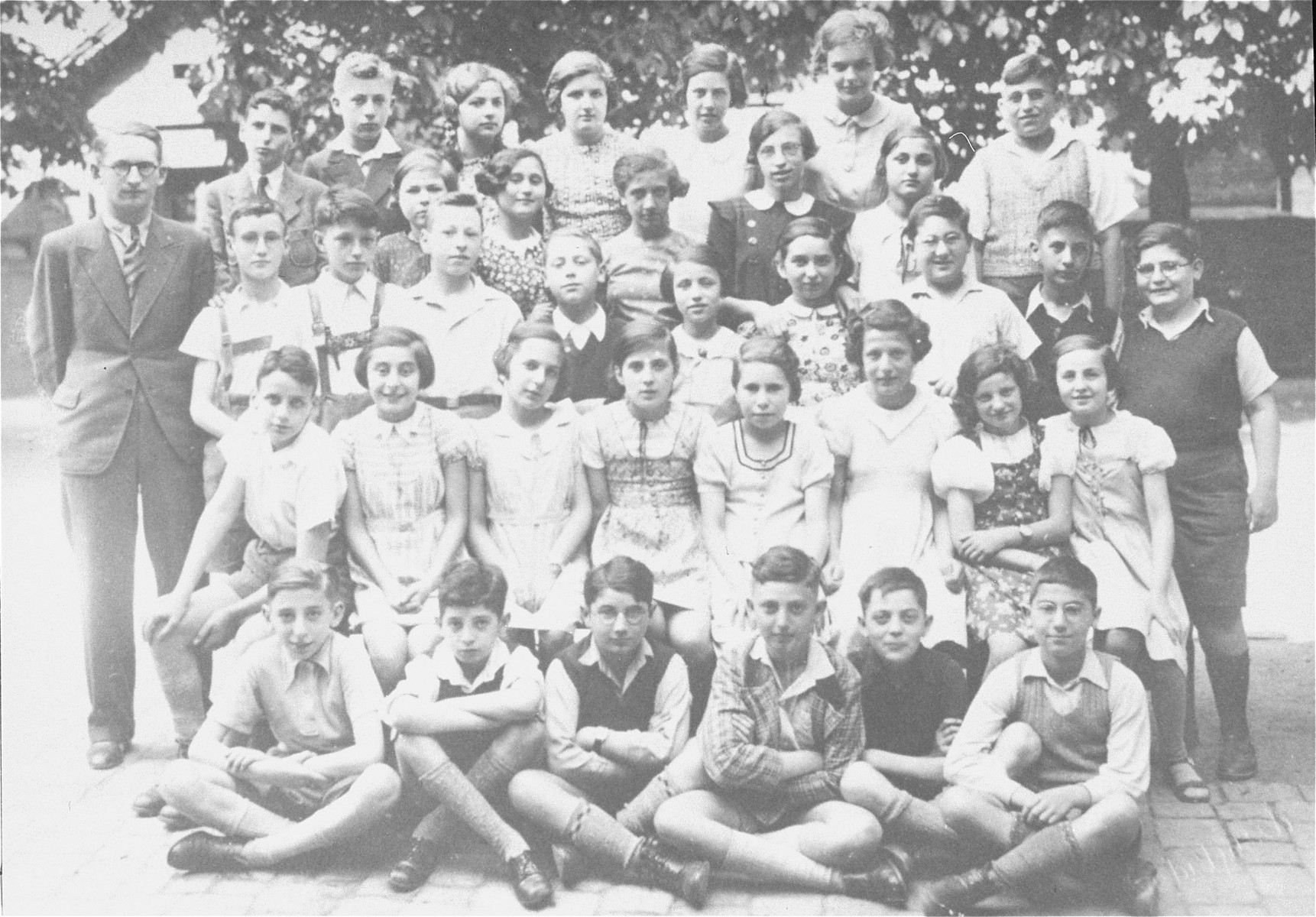 Group portrait of pupils in the seventh grade at a Jewish school in Karlsruhe, Germany that had been relocated to one floor at the 'Holzbodengymnasium' a special school for mentally disabled children.   Among those pictured is the teacher, Max Ottensoser.  Also pictured is Suse Heidenheimer (later Steinhardt),  second row from the front and the fourth girl from the right.  Louis (Ludwig) Maier is pictured in the top row, second from the left.  Julius Hirschberger is on the borttom row, far right and Walter Baer is in the third row, third from the left.