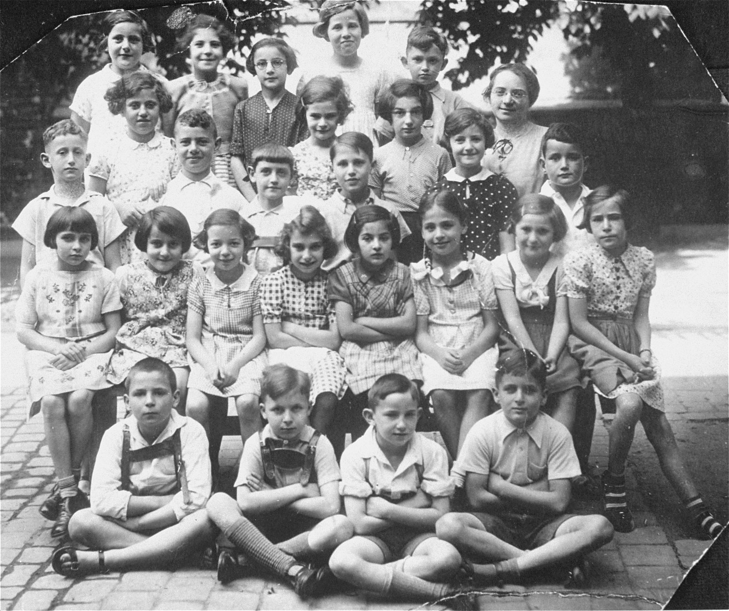 Group portrait of pupils in the third grade at a Jewish school in Karlsruhe, Germany that had been relocated to one floor at the 'Holzbodengymnasium' a special school for mentally disabled children.   Among those pictured is the teacher, Caecilie Schweizer.
