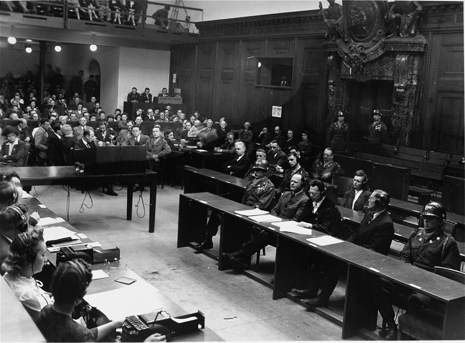 View of the courtroom during a session of the Milch Trial.  Former Field Marshal Erhard Milch is seated at the right in the front row, second from the left.  He is seated to the left of his two lawyers, Dr. Friedrich Bergold and Dr. Werner Milch.