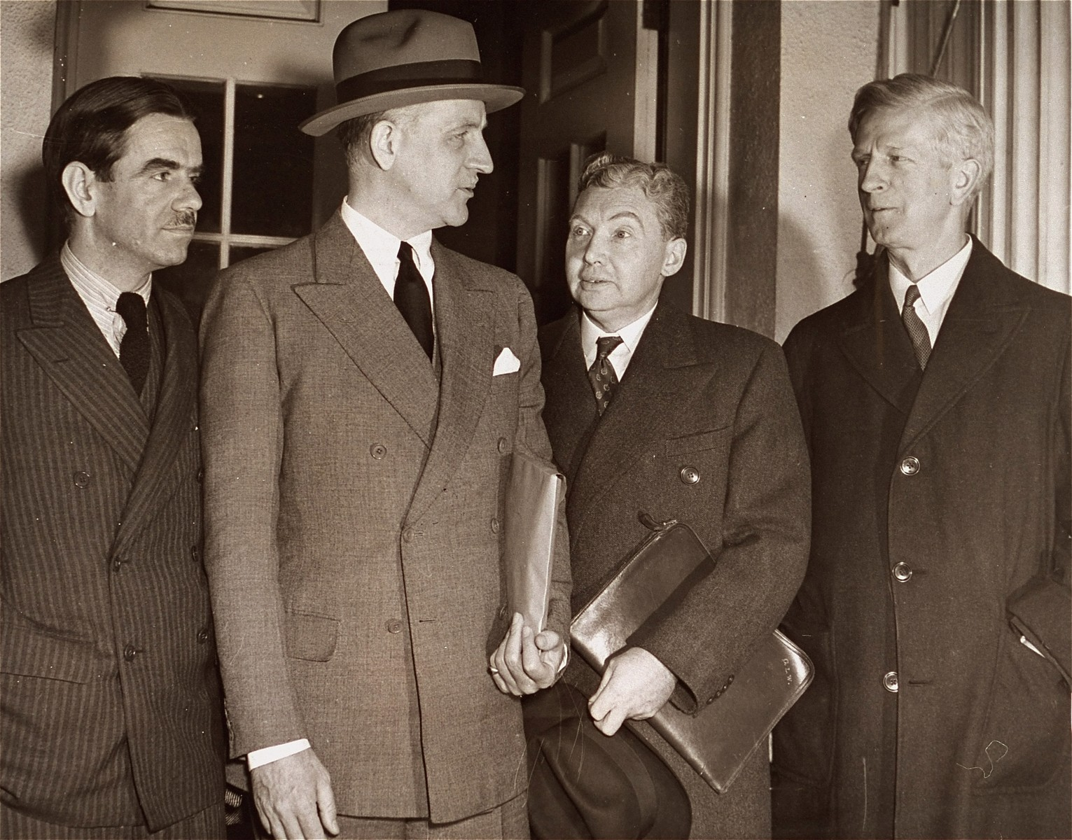 "Members of the President's Advisory Committee on Political Refugees pose with Under Secretary of State Sumner Welles after their meeting at the White House with Roosevelt.  Pictured from left to right are: Hamilton F. Armstrong, Sumner Welles, committee secretary George L. Warren, and committee chairman, James McDonald.  Original  AP caption reads: ""With tense relations existing between nations over handling of minorities, the National Advisory Committee on Refugees reported to President Roosevelt in Washinton, D.C. Nov. 16 at the White House.  From the left: Committeeman Hamilton F. Armstrong; Under Secretary of State Sumner Welles who sat in on the meeting; Secretary of Committee George L. Warren and Chairman James Mac Donald [sic]."""