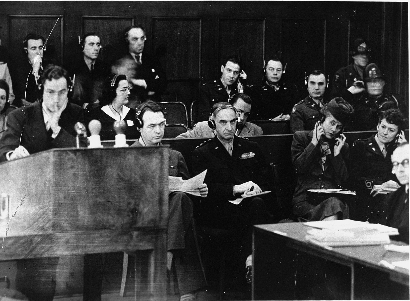 American prosecutor James M. McHaney (left) at the podium during the Pohl/WVHA trial.  Behind him from left to right are Brigadier General Telford Taylor, US Military Governor Lucius Clay, and Clay's wife.