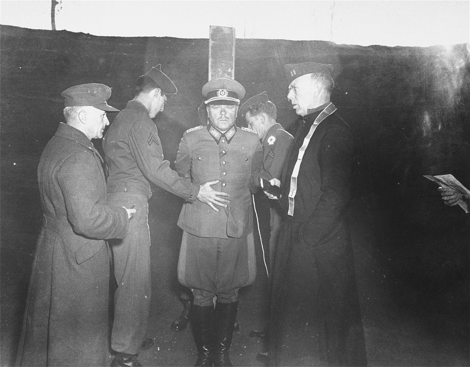 "American troops prepare Major General Anton Dostler for execution.  Dostler was executed for having ordered the shooting of 15 U.S. soldiers captured behind German lines in March 1944.  The Americans were on a sabotage mission and according to the Hague Convention should have been treated as prisoners of war upon their capture.  Dostler, however, claimed in his defense that he was simply carrying out orders, the so-called ""Commando Order,"" he and other German officers had received directly from Adolf Hitler to execute Allied troops captured in German-occupied territory if they were on intelligence or sabotage missions.  The court martial's denial of Dostler's defense set an important precedent for the trial of Nazi war criminals several months later at Nuremberg because it did not allow the accused to claim in their defense that they were only following orders."