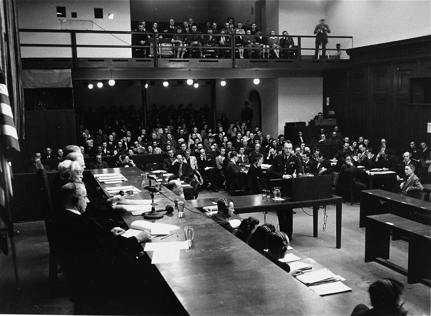 The courtroom in the Palace of Justice during the Flick Trial.    US Chief of Counsel Brigadier General Telford Taylor is shown at the podium in the center, and the Tribunal is on the left.  The spectators gallery is at the back.