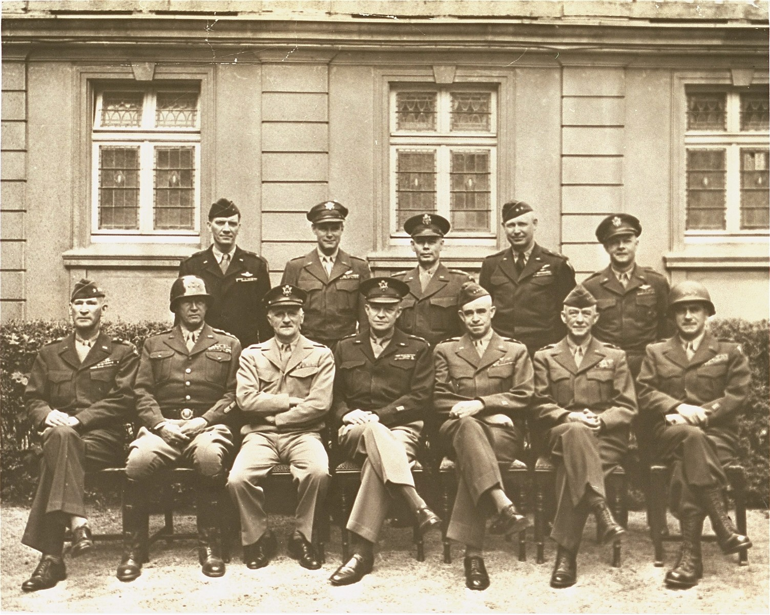 American generals who helped pave the way to victory are photographed during a victory meeting at Gen. Omar N. Bradley's 12th Army group headquarters.   Seated left to right: Lt. Gen. Wm. H. Simpson, Gen. George Patton, Jr., Gen. Carl A. Spaatz, Gen. Dwight D. Eisenhower, Gen. Omar N. Bradley, Gen. Courtney H. Hodges, Lt. Gen. Leonard T. Gerow. Standing left to right: Brig. Gen. Ralph F. Stearley, Lt. Gen. Walter B. Smith, Maj. Gen. Otto P. Weyland, Brig. Gen. Richard E. Nugent.