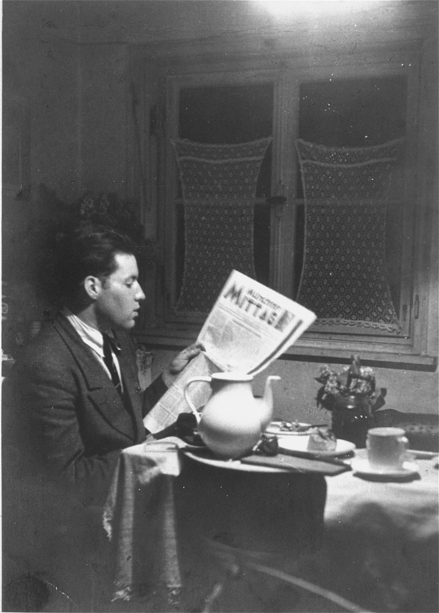 Solly Perel reads a newspaper in his room in Munich just prior to his departure for Palestine.