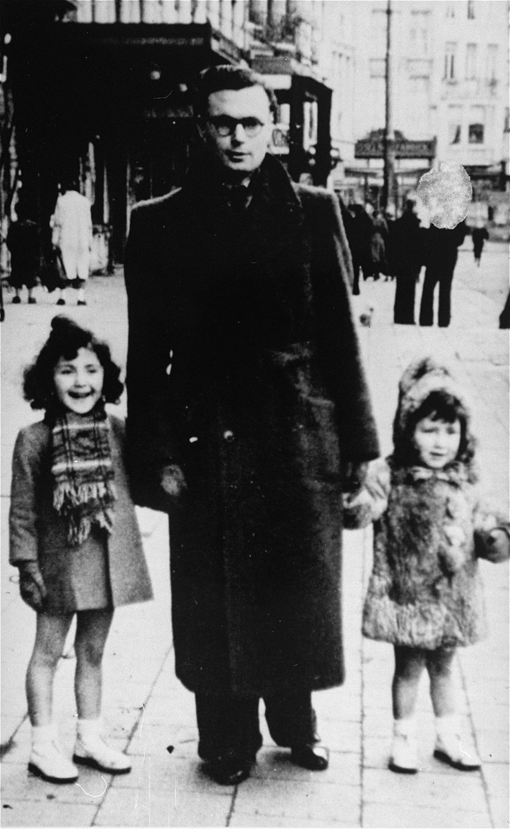 Annette and Margo Lederman, two Jewish children in hiding, pose with one of the sons of their rescuers on a street in Rumst, Belgium.