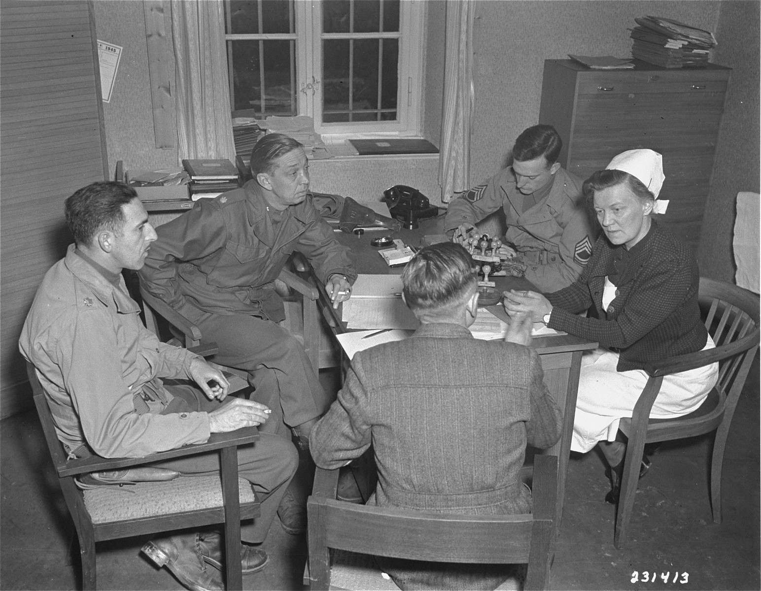 American war crimes investigators question chief nurse Irmgard Huber about the mass killings that occurred at the Hadamar Institute.  The photograph was taken by an American military photographer soon after the liberation.