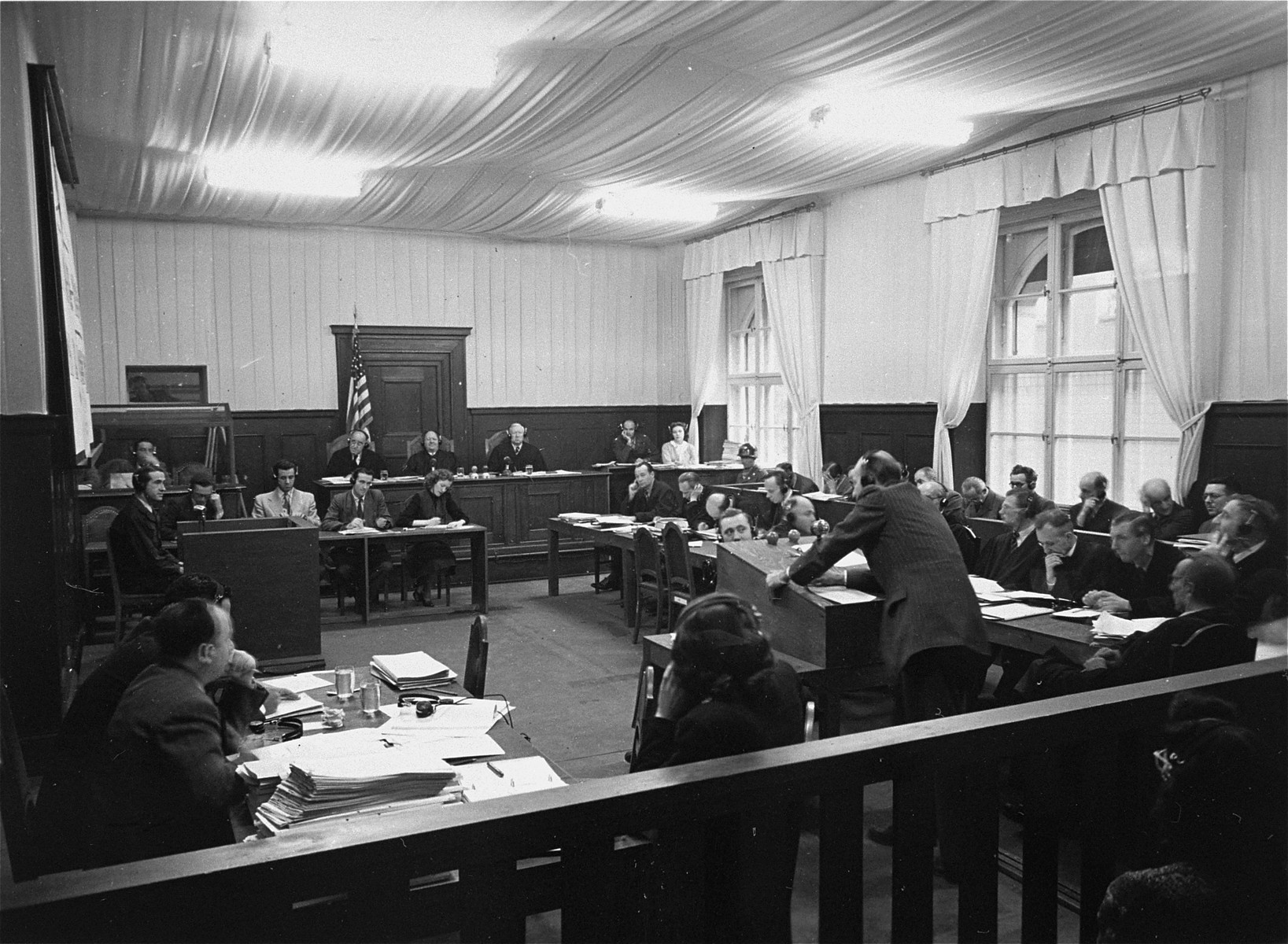 The proceedings of the RuSHA Trial in Courtroom #6 in the Palace of Justice.    In the back sits Military Tribunal I, to the right is the defendants' dock, and in front are the lawyers.  Sitting below the middle judge of the Tribunal is Vivien Putty Spitz, a court reporterr.