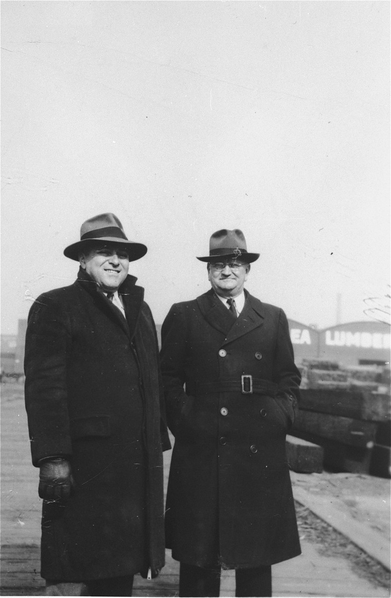 Two men responsible for acquiring the President Warfield standing in a dockside lumber yard in Baltimore, where the ship was prepared for its trip to Europe.  Pictured on the left is George Levin.