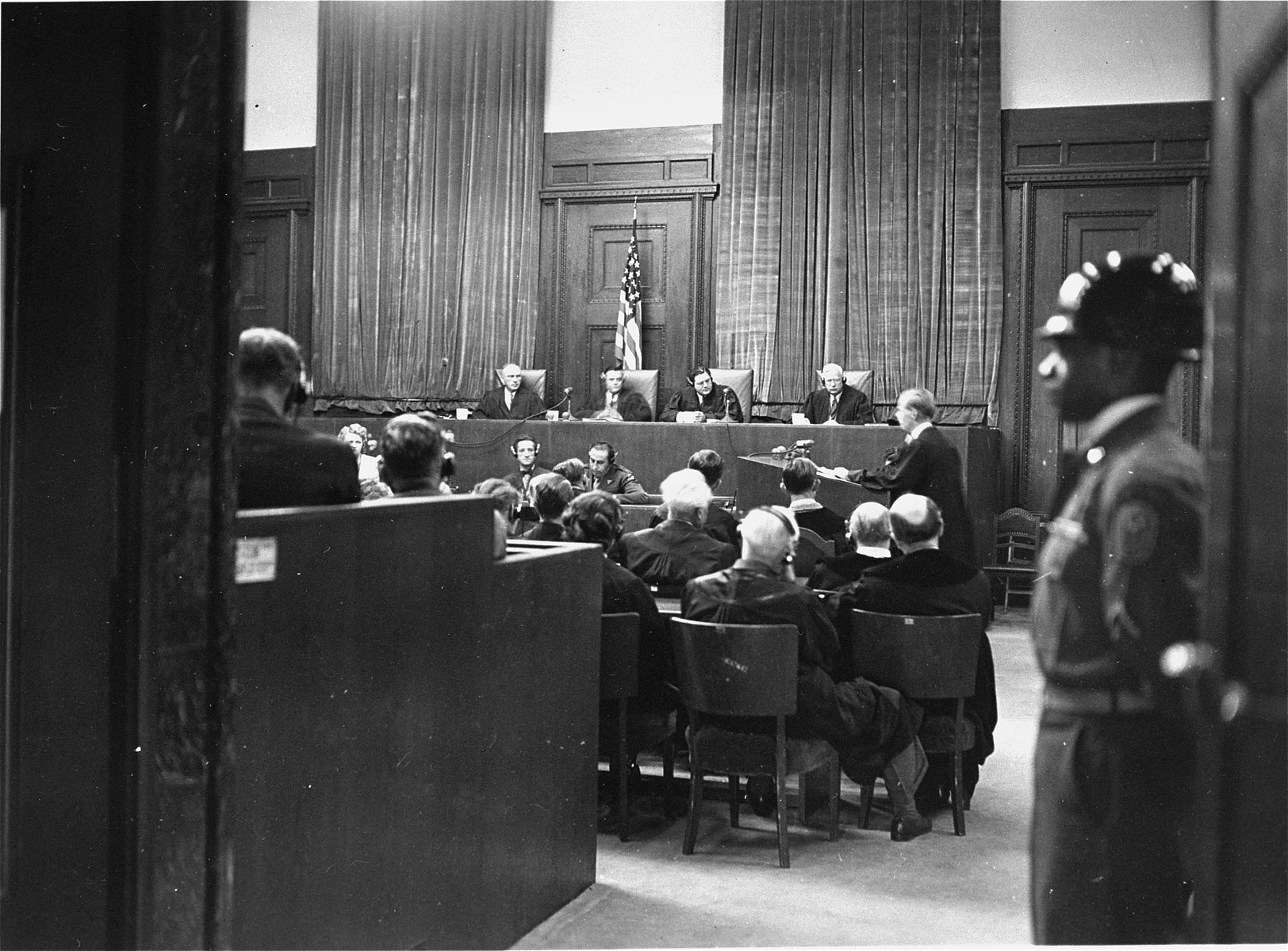 An American soldier guards the main entrance to the courtroom during the I.G. Farben Trial.  In the back sits the Military Tribunal VI.
